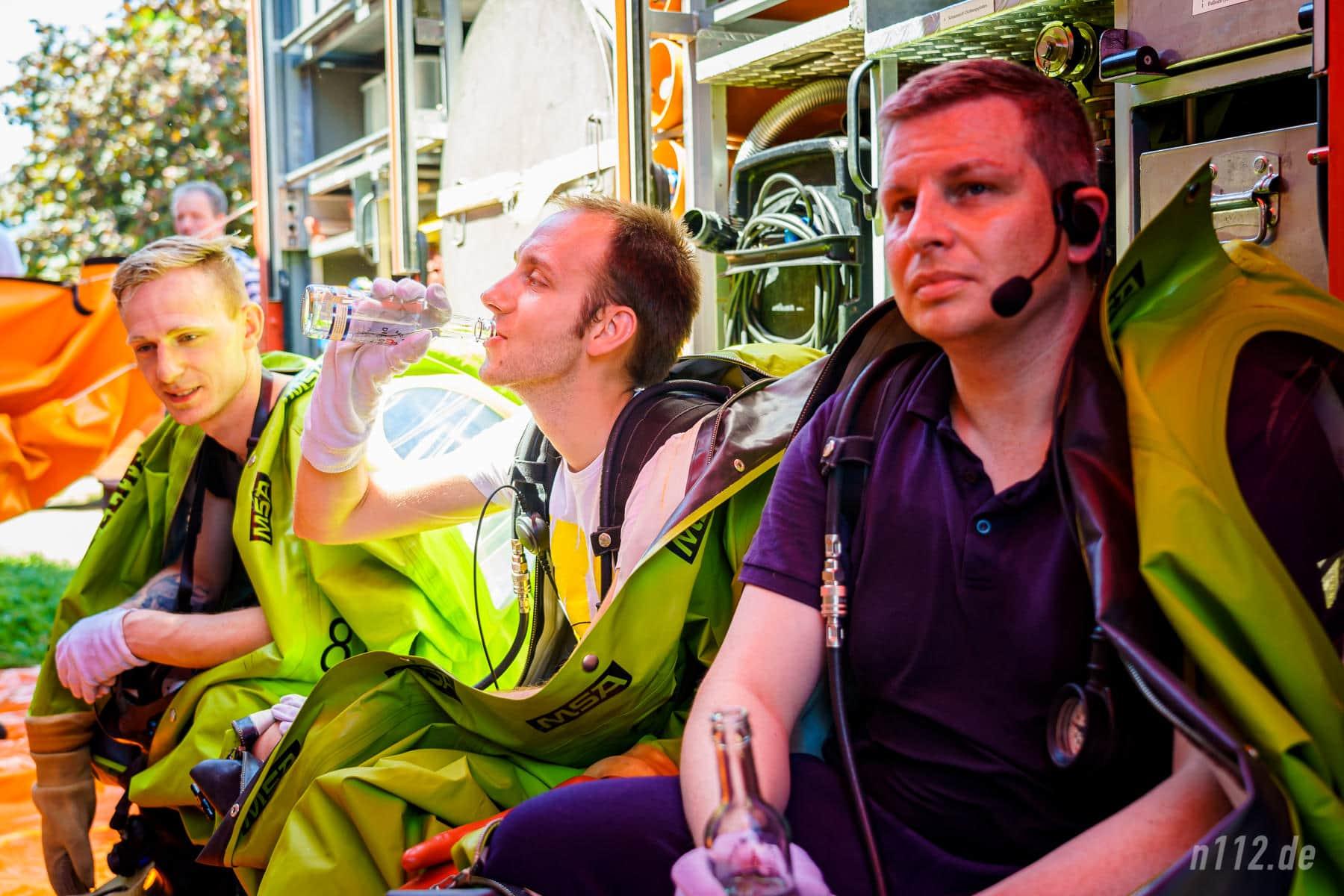 Schon beim Warten schweißgebadet: Ausgerüstet mit Vollschutzanzügen sitzen die Freiwilligen bei 33 Grad im Schatten unter einer Plane (Foto: n112.de/Stefan Simonsen)