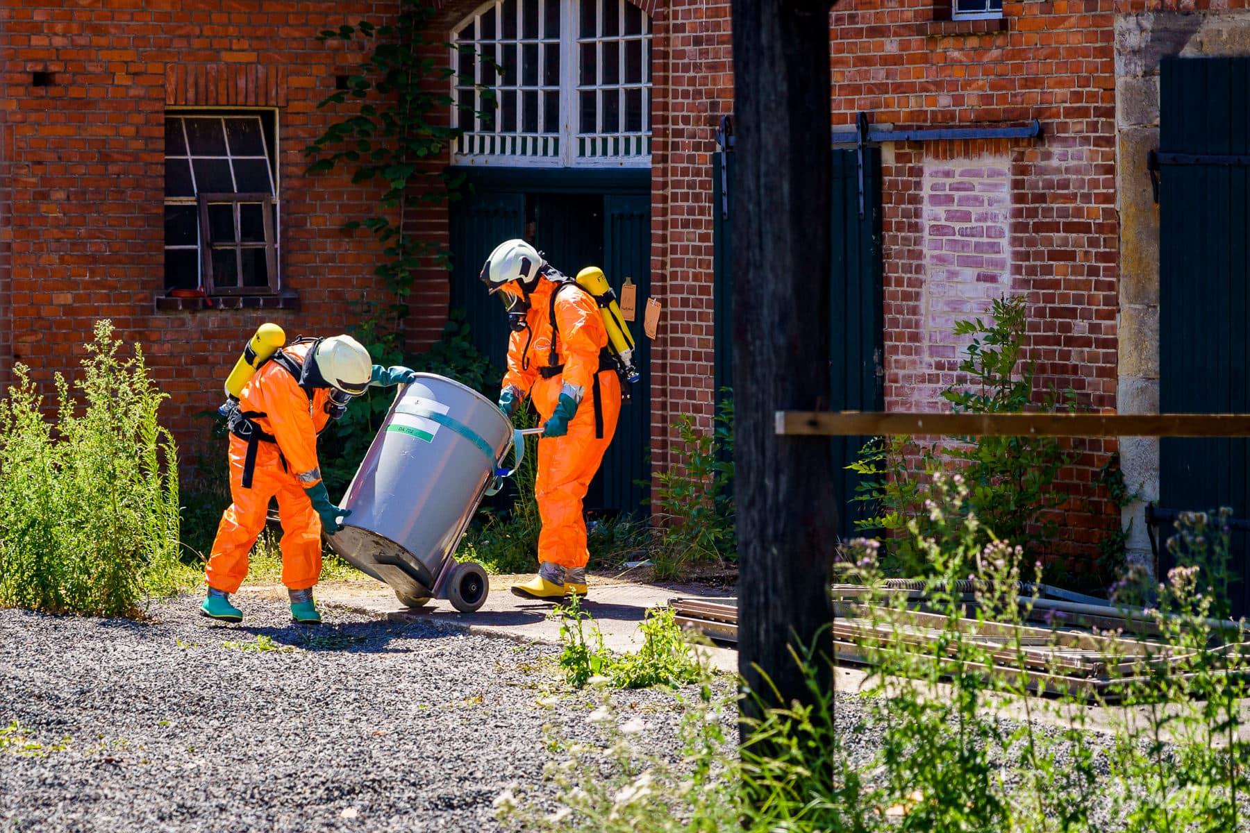 Mit leichten Schutzanzügen bergen zwei Feuerwehrleute das verschlossene Fass aus dem landwirtschaftlichen Anwesen (Foto: n112.de/Stefan Simonsen)