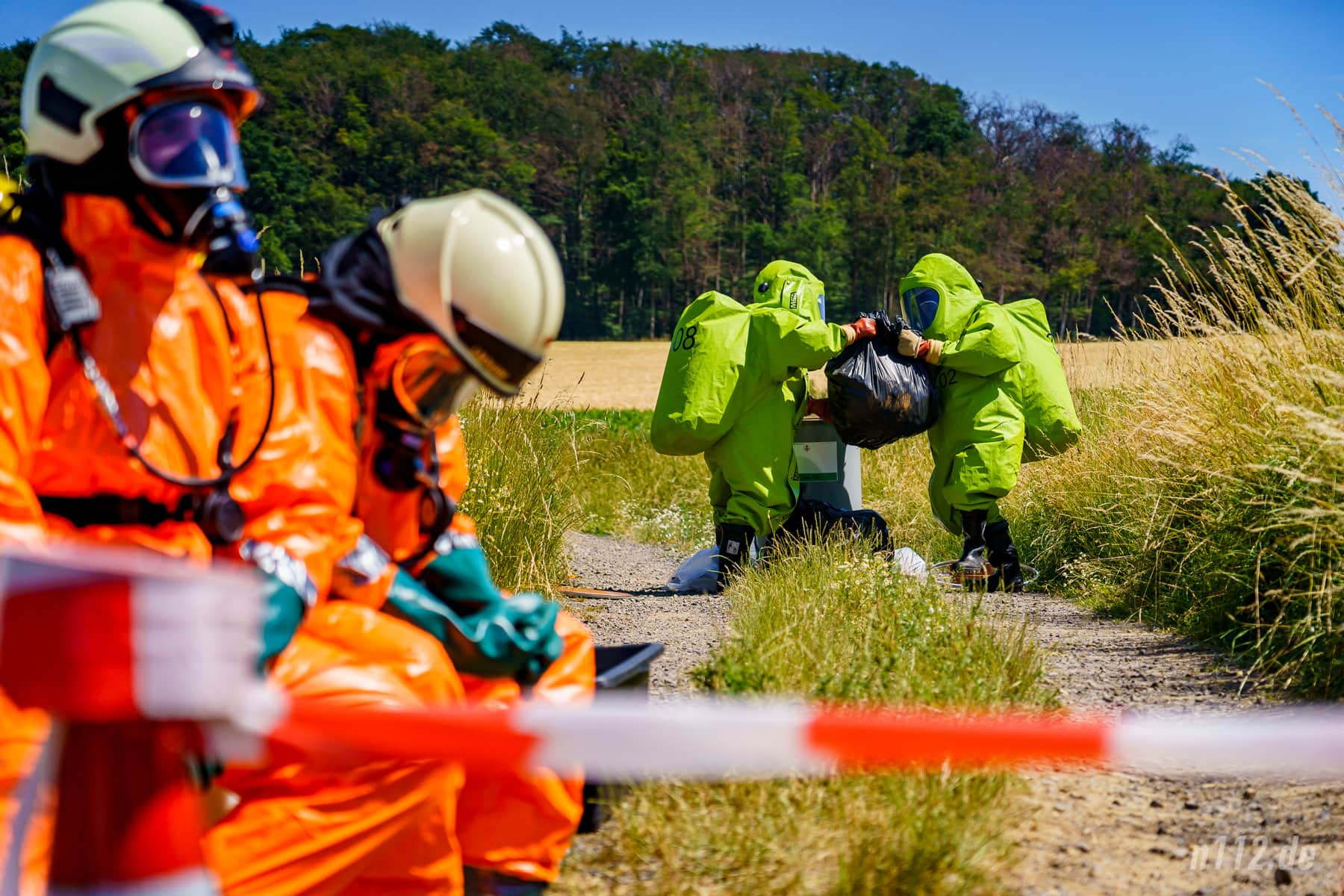 Nur Abfall: Das zweite Team findet keine giftige Substanz im Fass. Das erste Team wartet derweil im Vordergrund unter sengender Sonne, um im Notfall eingreifen zu können (Foto: n112.de/Stefan Simonsen