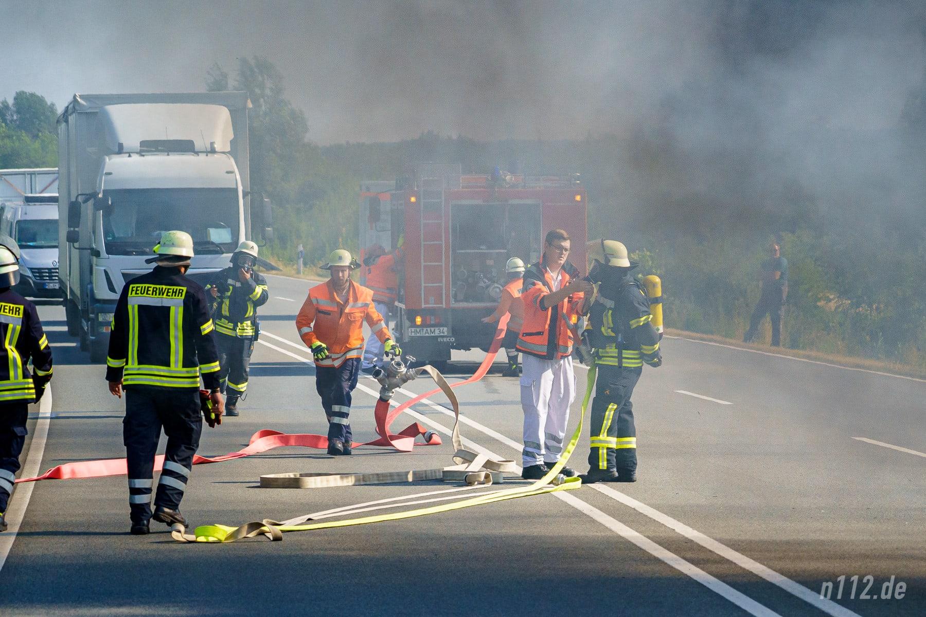 Außerhalb der Gefahrenzone: Die Sanitäter des Rettungswagens helfen beim Anlegen der Atemschutzgeräte und beim Aufbau des Löschangriffs (Foto: n112.de/Stefan Simonsen)