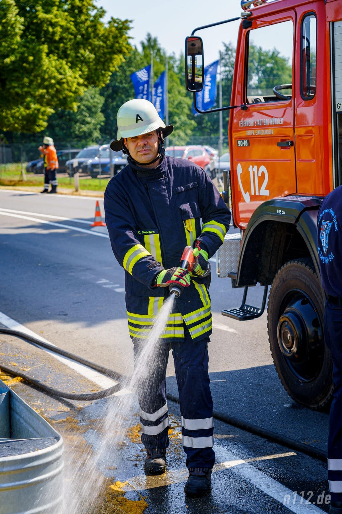 Trotz tropischer Hitze: In Schutzkleidung löscht ein Ehrenamtlicher den Grünstreifen an der B442 (Foto: n112.de/Stefan Simonsen)