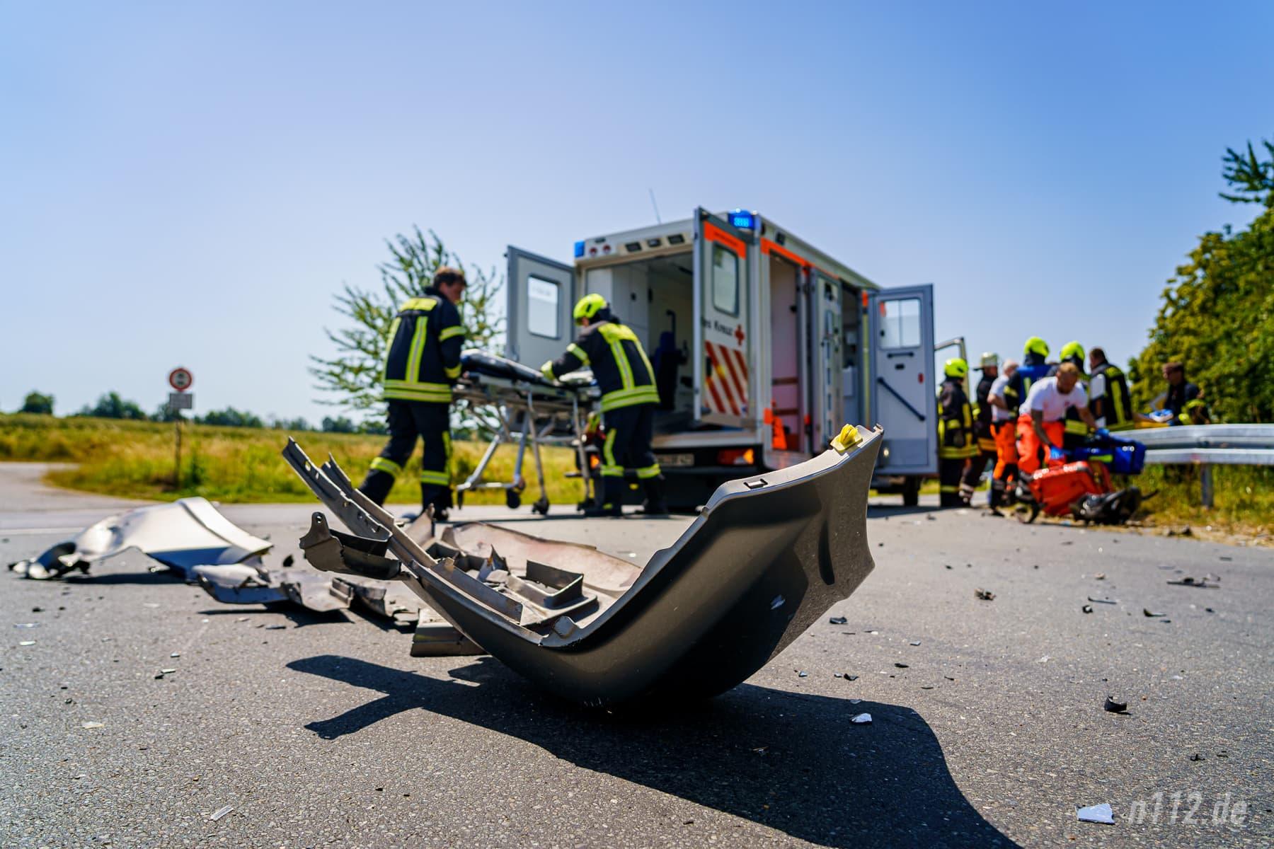 Die abgerissene Frontschürze des Autos liegt auf der Kreuzung - im Hintergrund tragen die Helfer den Verletzten aus dem Gebüsch zum Rettungswagen (Foto: n112.de/Stefan Simonsen)