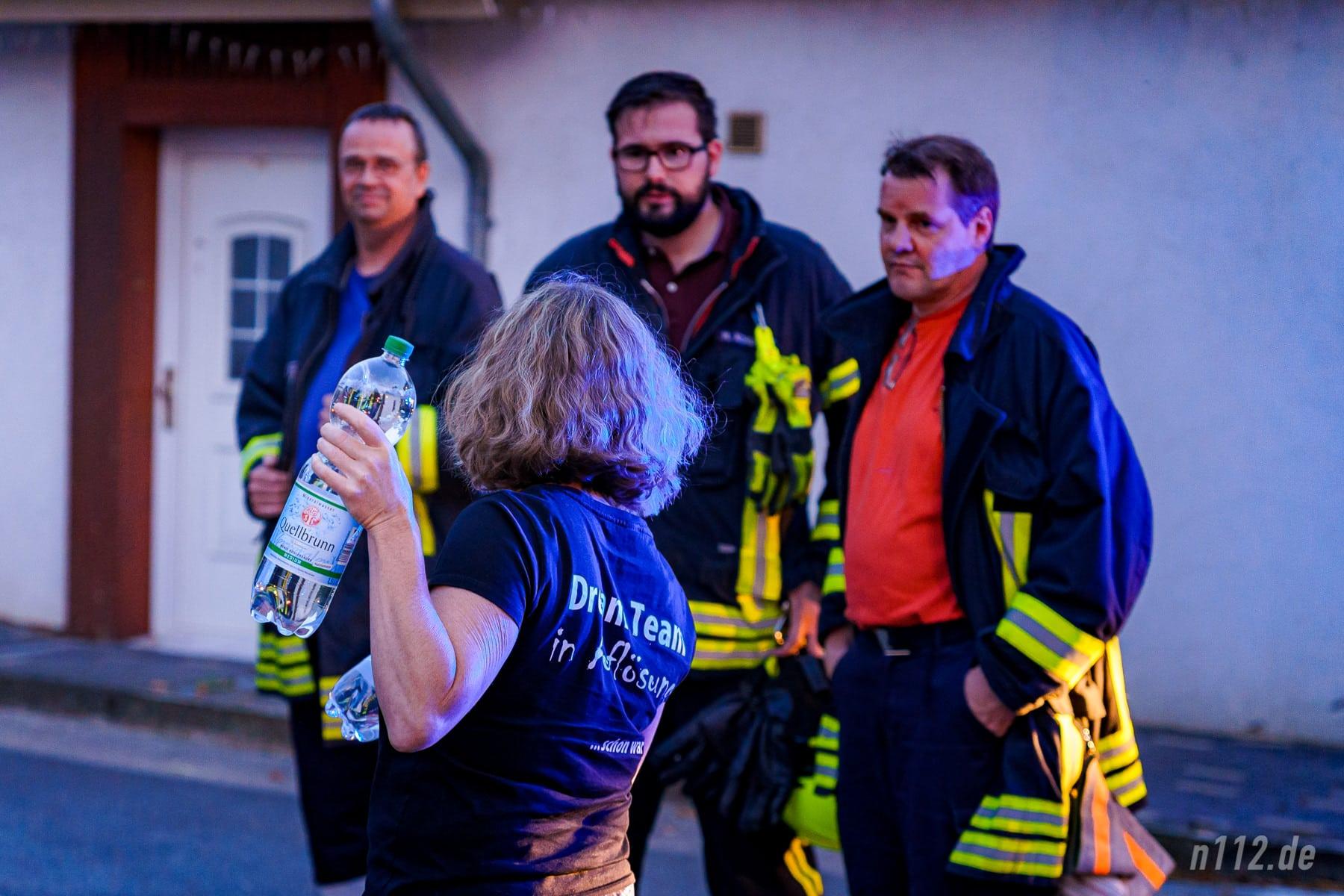 Eine Anwohnerin verteilt Wasserflaschen an die Feuerwehrleute (Foto: n112.de/Stefan Simonsen)