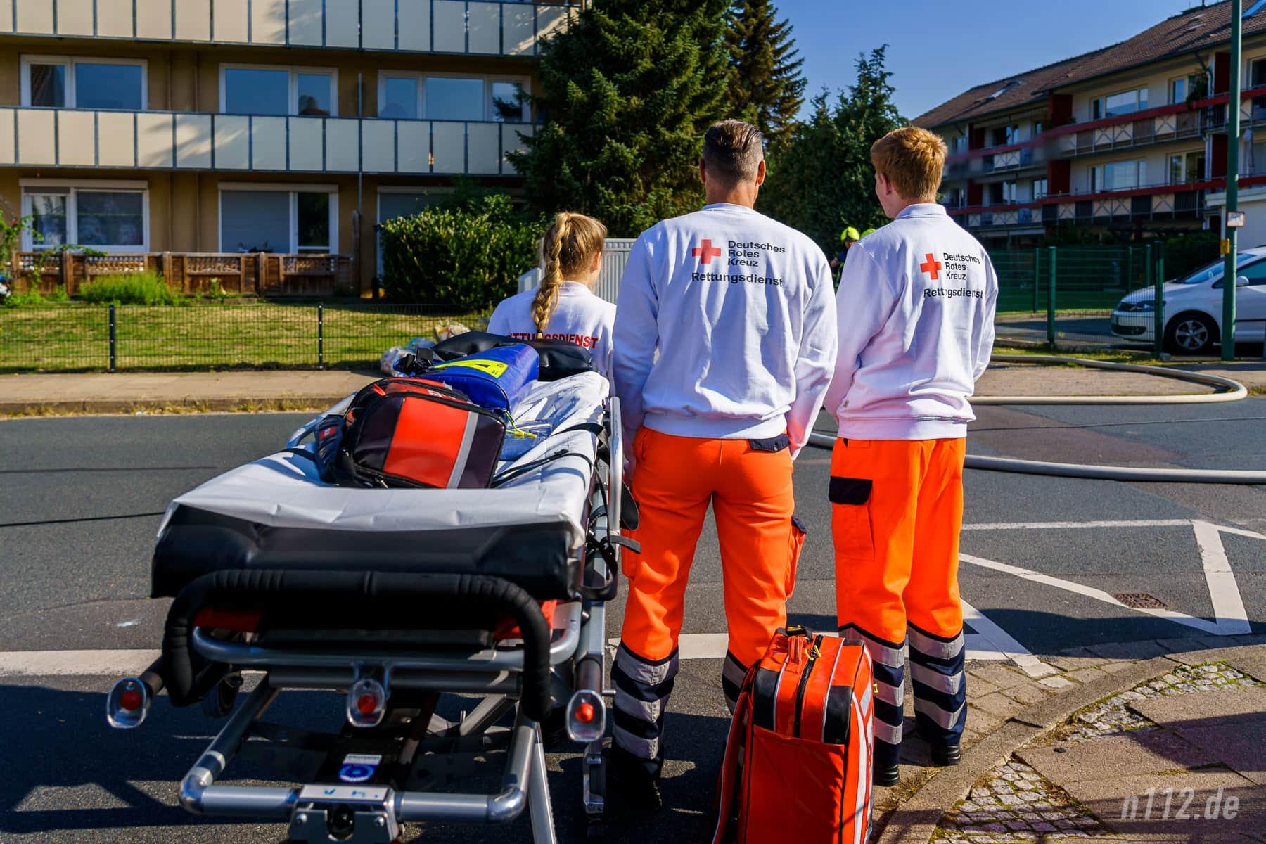 Warten auf Verletzte: Die Sanitäter stehen etwas abseits mit ihrem Equipment bereit. Ein Verletzter würde von Feuerwehrleuten aus dem Gefahrenbereich getragen und dann dort übergeben werden, wo der Rettungsdienst direkt mit der Behandlung anfangen kann (Foto: n112.de/Stefan Simonsen)