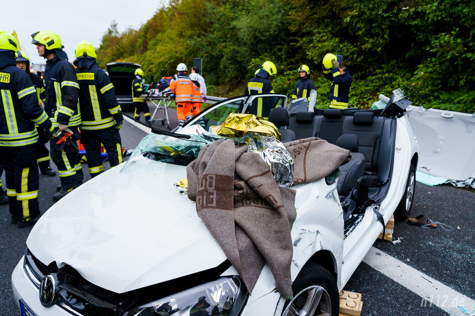 Das Autowrack nach der Rettung. Im Hintergrund wird der Fahrer zum Rettungswagen gebracht (Foto: n112.de/Stefan Simonsen)