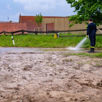 Feuerwehrleute reinigen nach einem heftigen Regenguss die Fahrbahn in Groß Holtensen von Schlamm (Foto: n112.de/Stefan Simonsen)