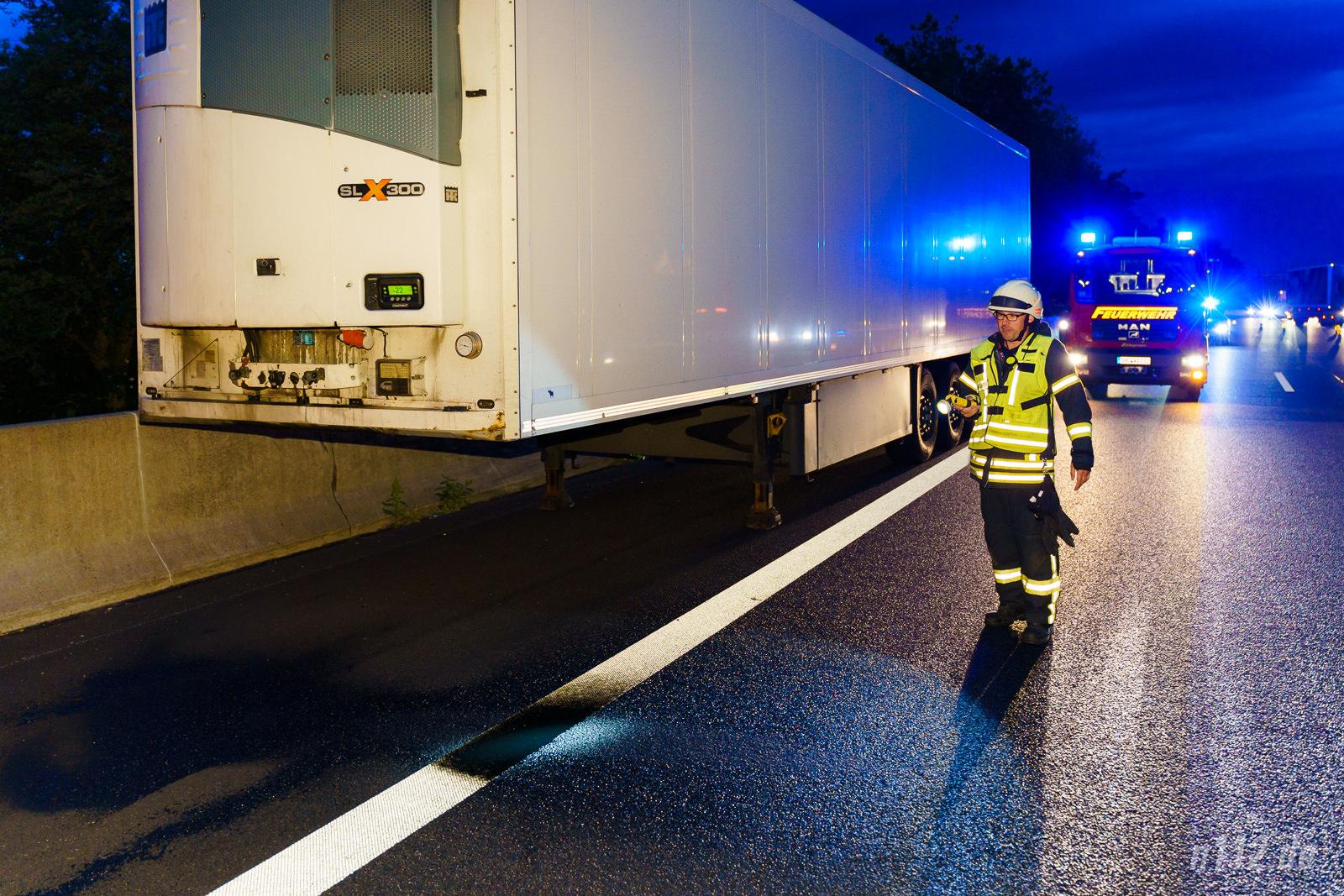 Der abgekoppelte Anhänger steht auf dem Standstreifen, ein Feuerwehrmann begutachtet eine Öllache (Foto: n112.de/Stefan Simonsen)