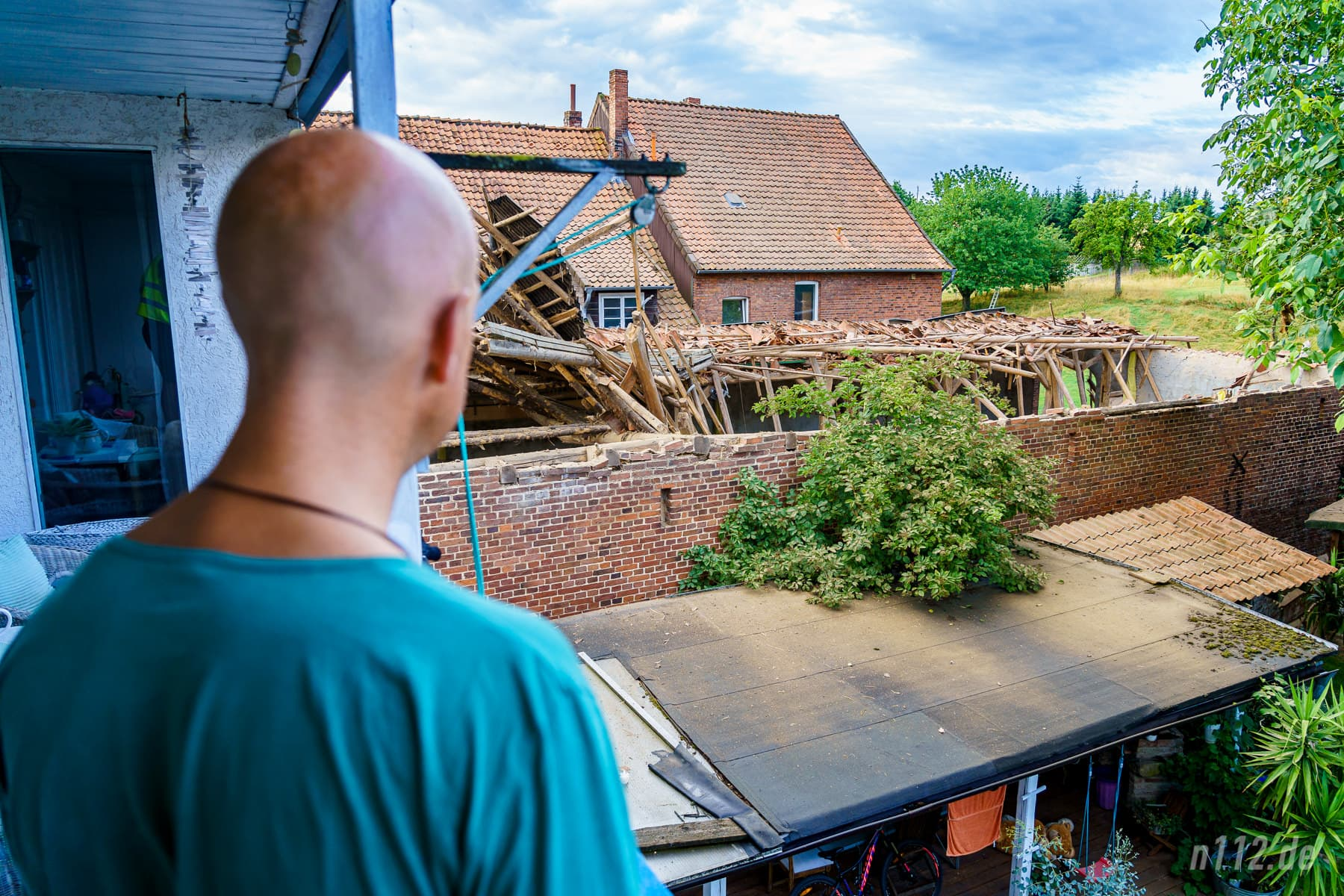 Ein Anwohner blickt auf das eingestürzte Dach, das schon zwei Tage lang ungewöhnliche Geräusche von sich gegeben haben soll (Foto: n112.de/Stefan Simonsen)