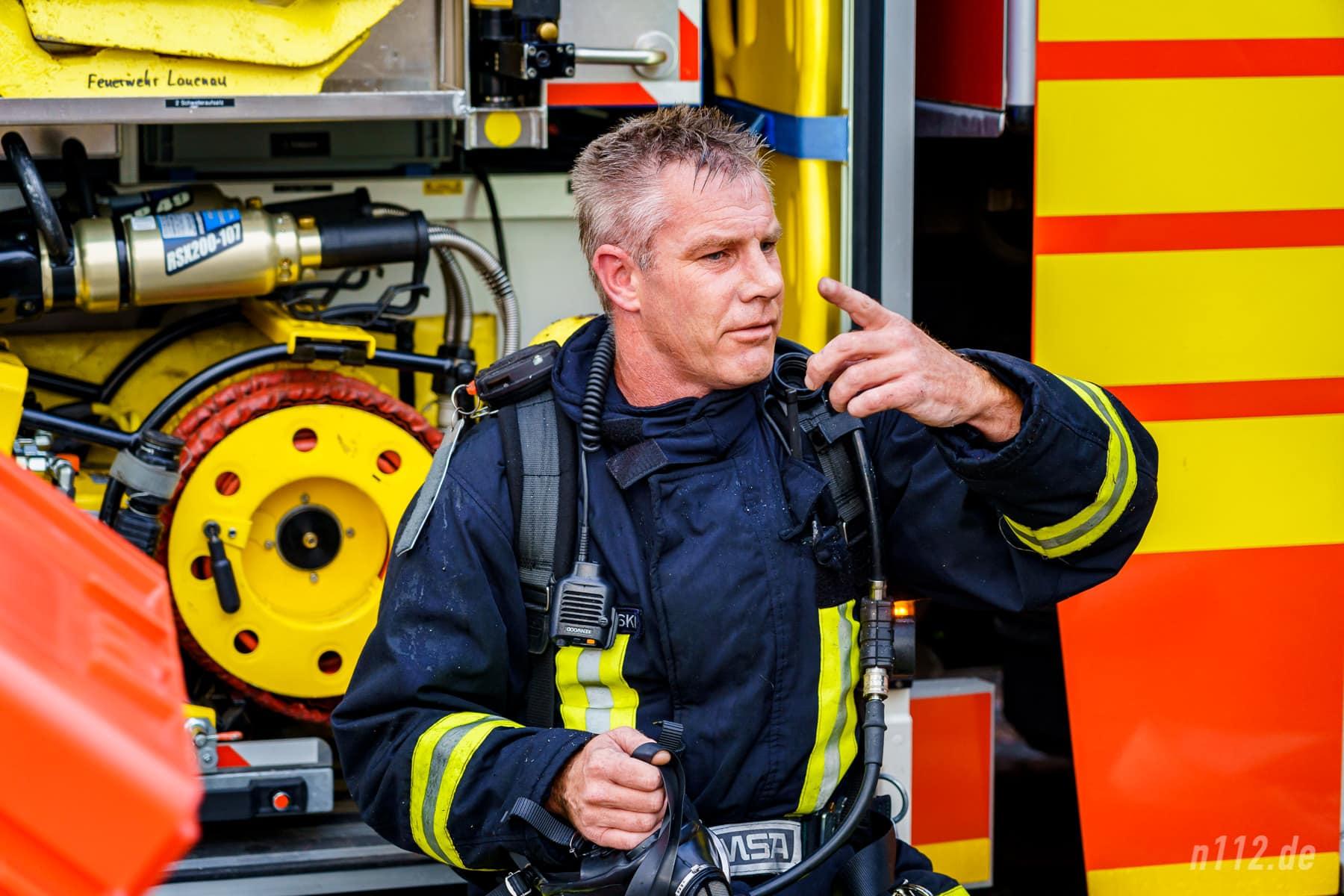 Ordentlich verschwitzt und mit verrauchter Einsatzkleidung sitzt dieser Feuerwehrmann nach seinem Einsatz unter Atemschutz an einem Löschfahrzeug (Foto: n112.de/Stefan Simonsen)