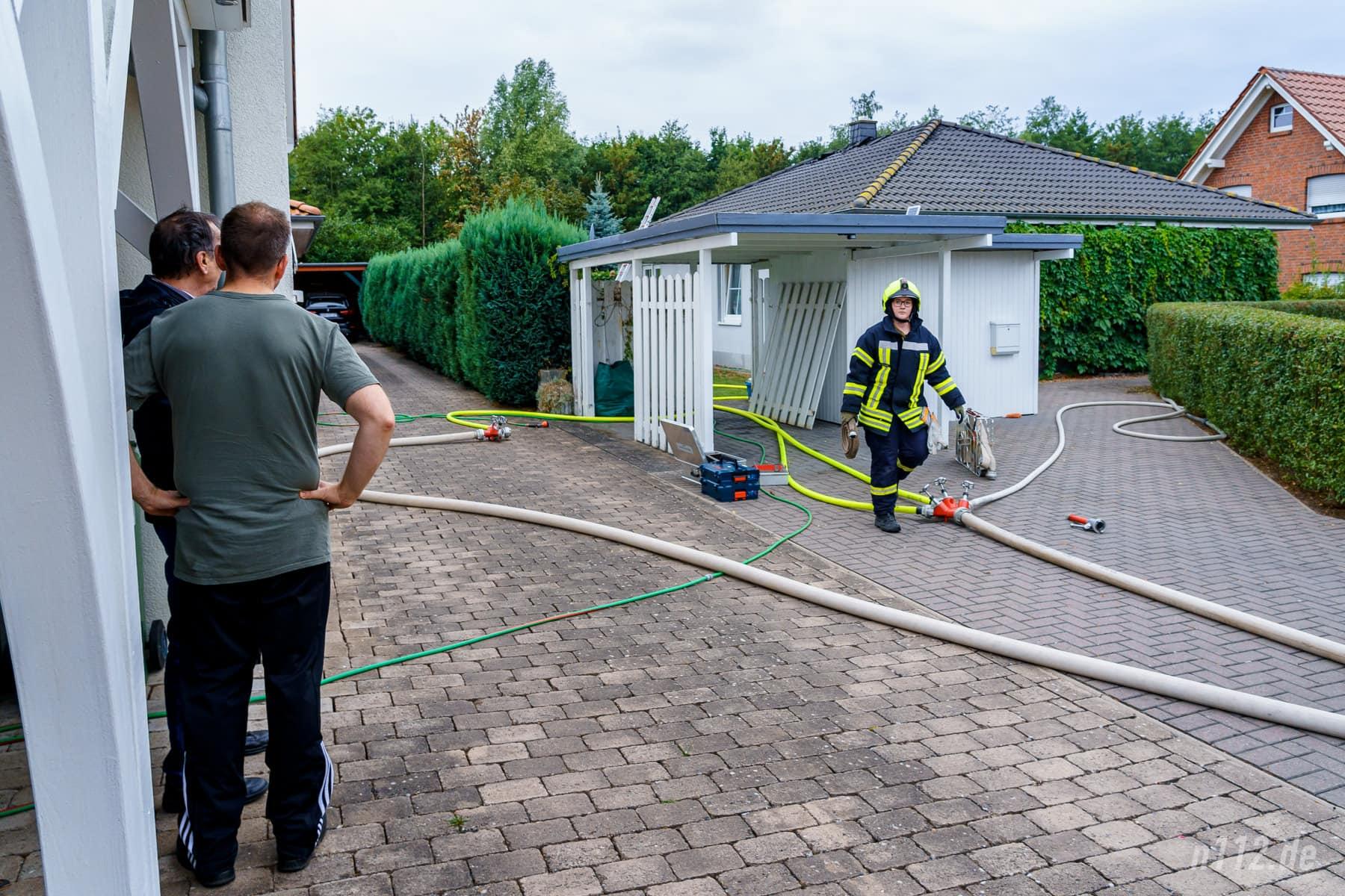 Nachbarn beobachten die Löscharbeiten. Sie hatten die verletzte Frau aus dem Rauch geführt und erste Löschversuche unternommen (Foto: n112.de/Stefan Simonsen)
