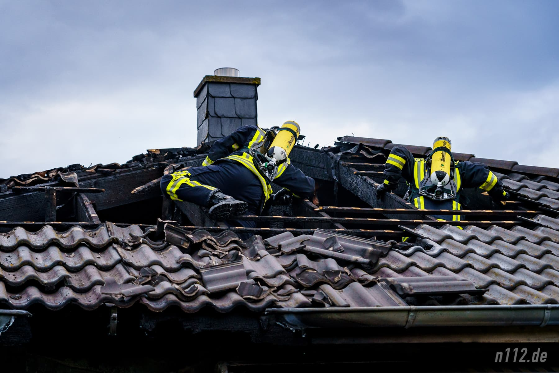 Feuerwehrleute löschen letzte Glutnester im Dach (Foto: n112.de/Stefan Simonsen)