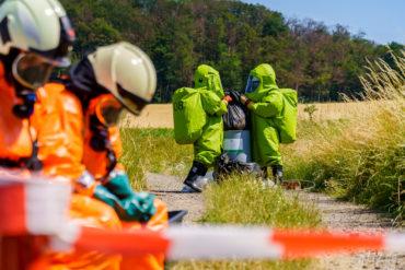 Unter brennender Mittagssonne untersuchten zwei ehrenamtliche Gefahrgutexperten der Feuerwehr ein Fass, das zuvor aus einer Scheune getragen worden war. (Foto: n112.de/Stefan Simonsen)