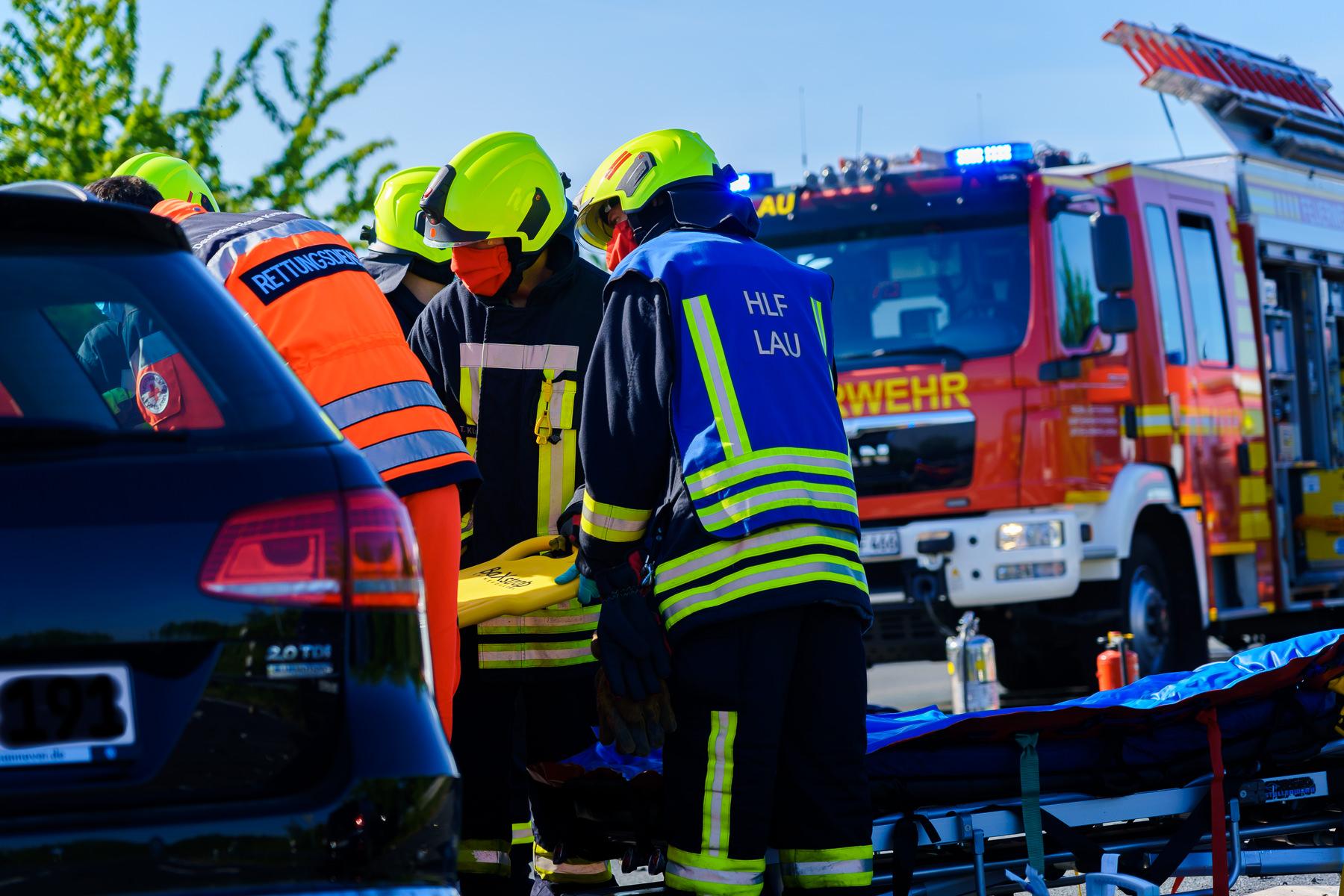 Ehrenamtliche Feuerwehrleute halten das Spineboard, während der Rettungsdienst die Verletzte aus dem Auto rettet.